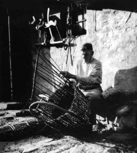 Košikár pri pletení koša na sečku